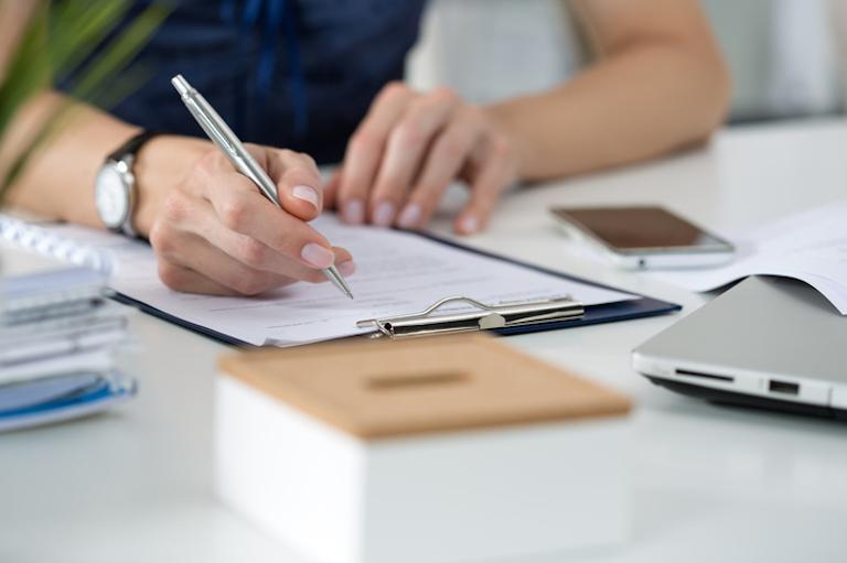 osoba pisząca nakartce umieszczonej wteczce